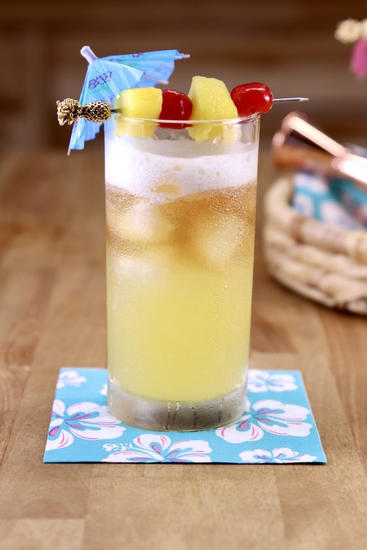 Mai Tai Cocktail with drink umbrella, pineapple cherry garnish in a collins glass
