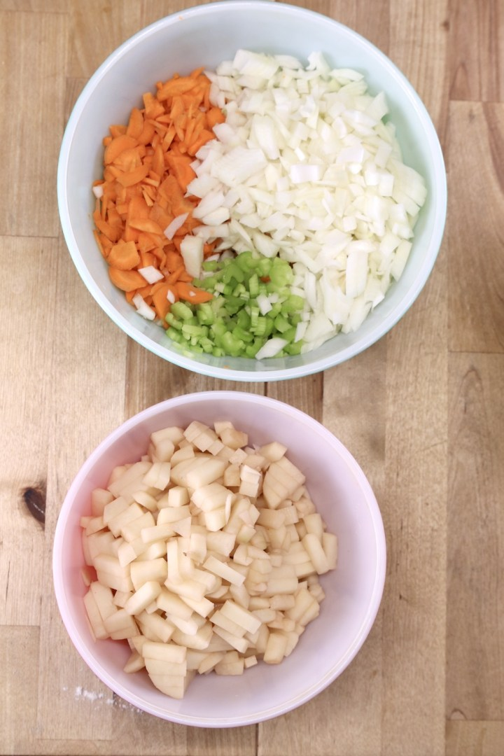 Bowl of diced carrots, celery, onions. Bowl of diced potatoes
