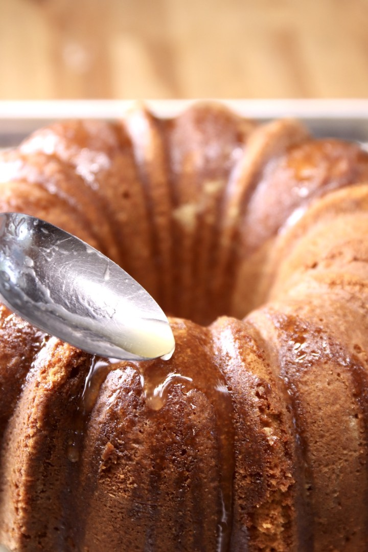 pouring glaze over pound cake with a spoon