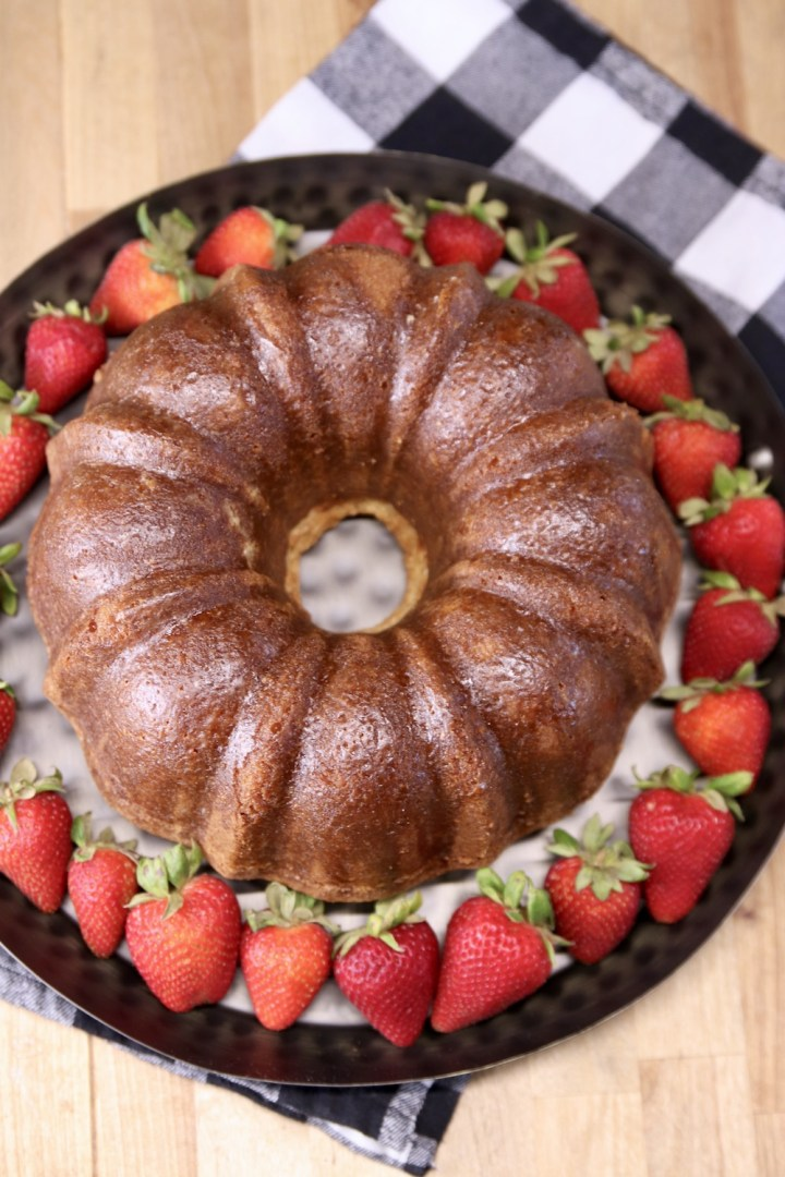 Amaretto Pound Cake - Bundt cake on a tray with fresh strawberries