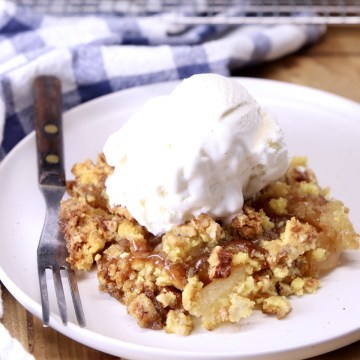 apple dump cake on a plate with a scoop of vanilla ice cream