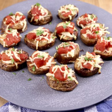 bruschetta topped potatoes on a platter