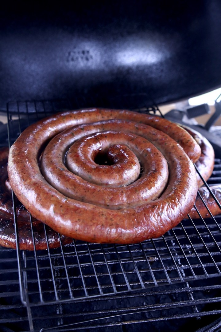 coil of smoked sausage on a grill