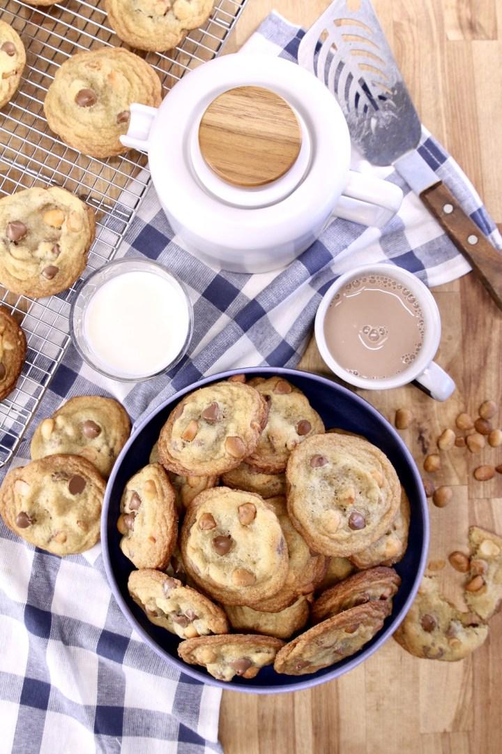 chocolate chip cookies in a bowl, tea pot, glass of milk, mug of hot chocolate