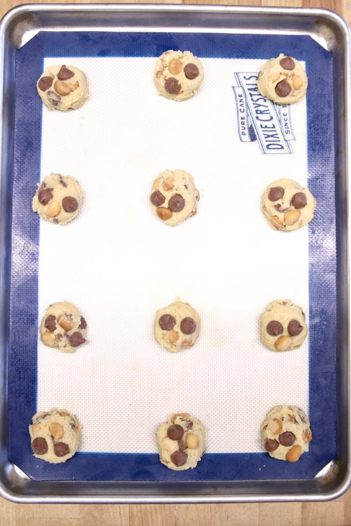 scoops of cookie dough on a lined baking sheet