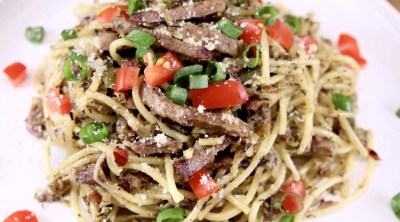 plate of brisket spaghetti with green onions and diced tomatoes