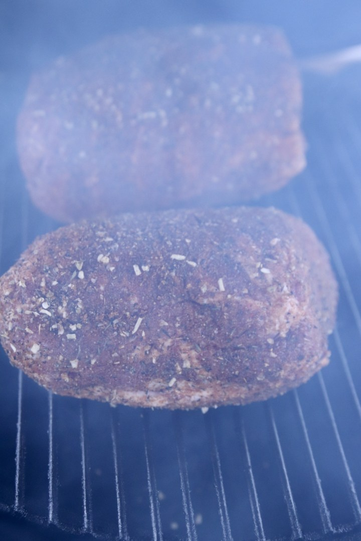 2 pork shoulder roasts on a grill with smoke