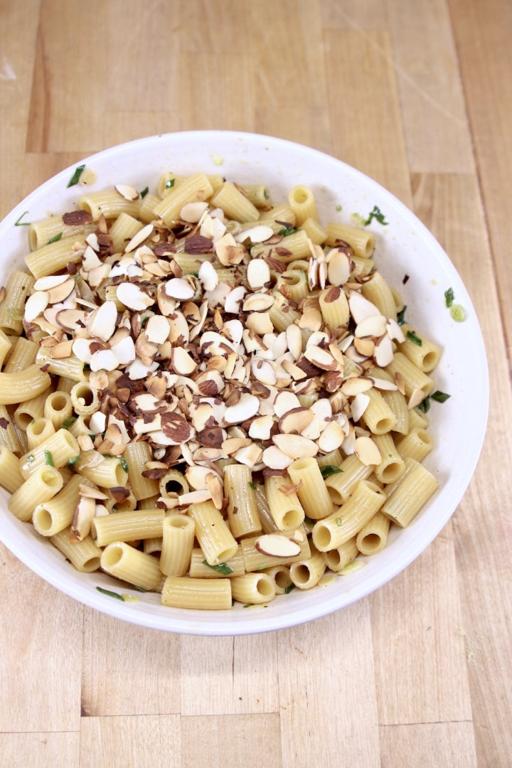 toasted sliced almonds over pasta salad in a white bowl