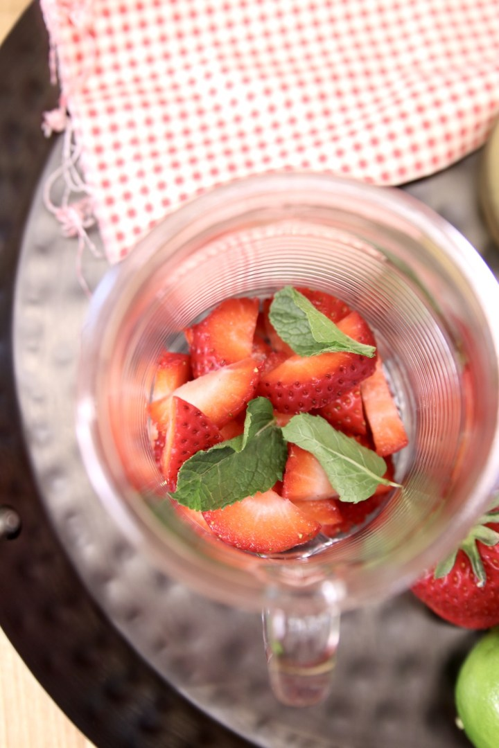 glass with sliced strawberries and fresh mint leaves for a mojito cocktail