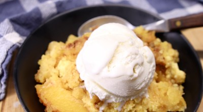 Peach Dump Cake served in a black bowl, topped with vanilla ice cream