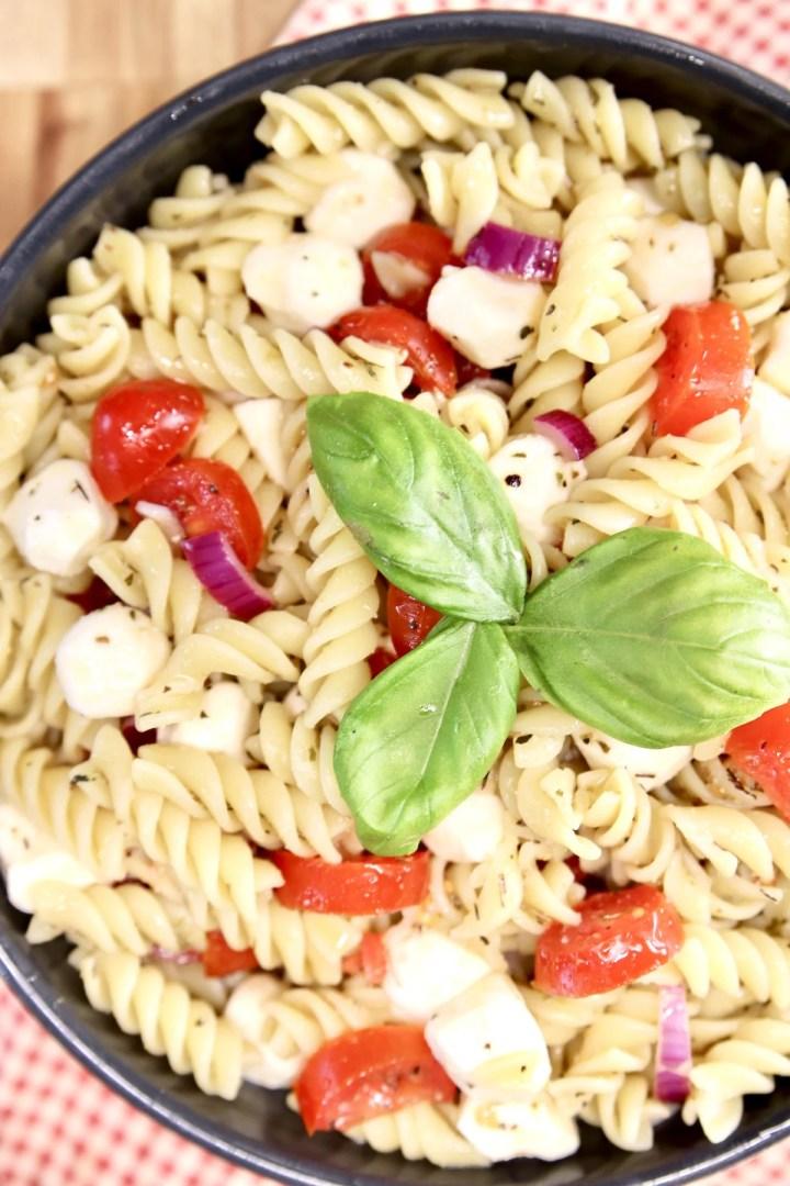 Tomato Mozzarella Pasta Salad with basil garnish