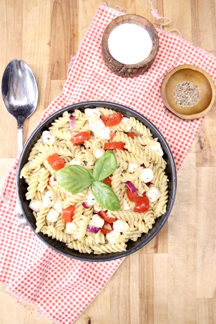 Pasta salad with tomatoes and basil , bowl of salt and pepepr