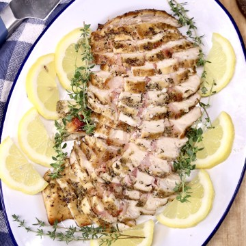 sliced chicken breast on a platter with lemon slices and thyme garnish