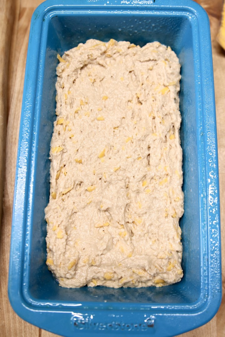 blue loaf pan filled with beer bread batter