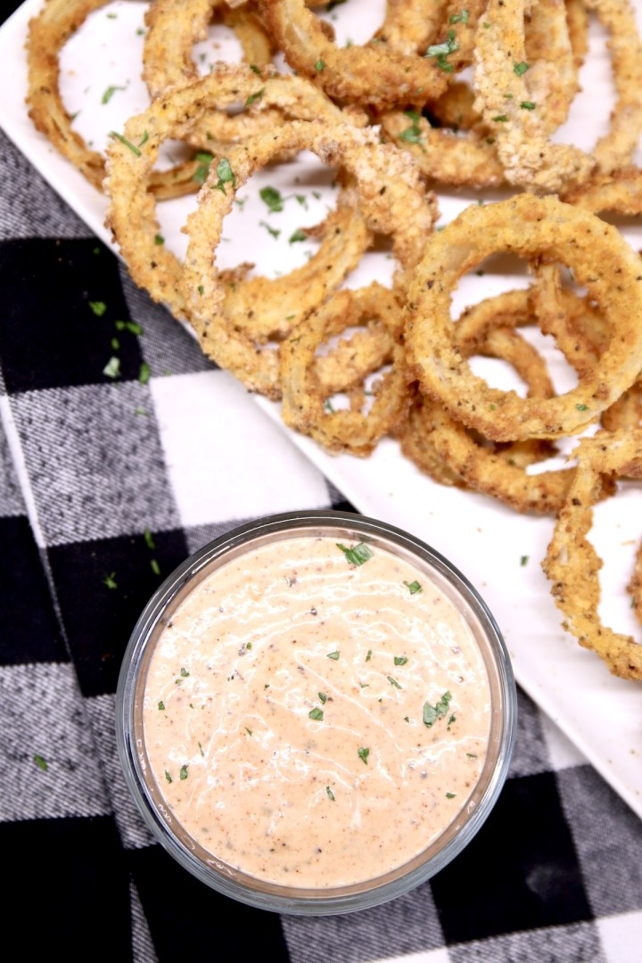 Onion rings on a platter with dipping sauce in a bowl