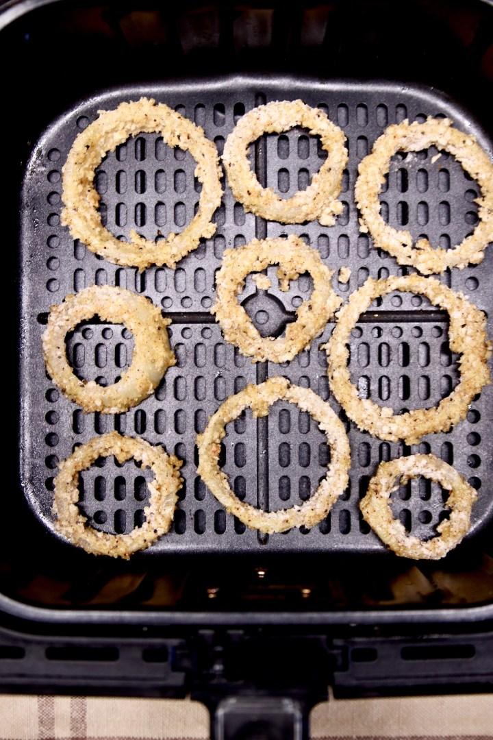 onion rings in an air fryer basket