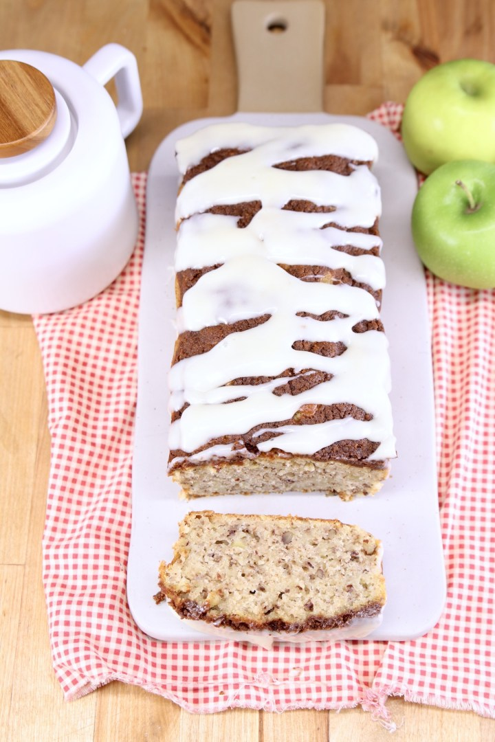 board with apple bread, once slice off of the end, tea pot, 2 apples