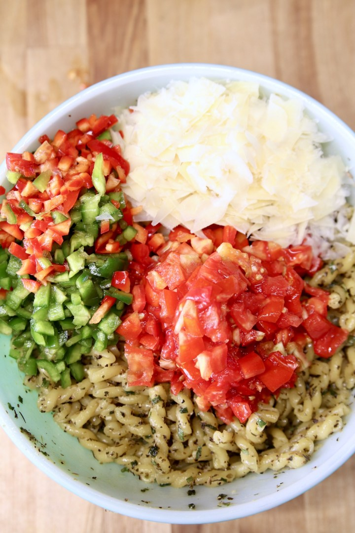 bowl of pasta topped with chopped tomatoes, bell peppers and shaved Parmesan cheese