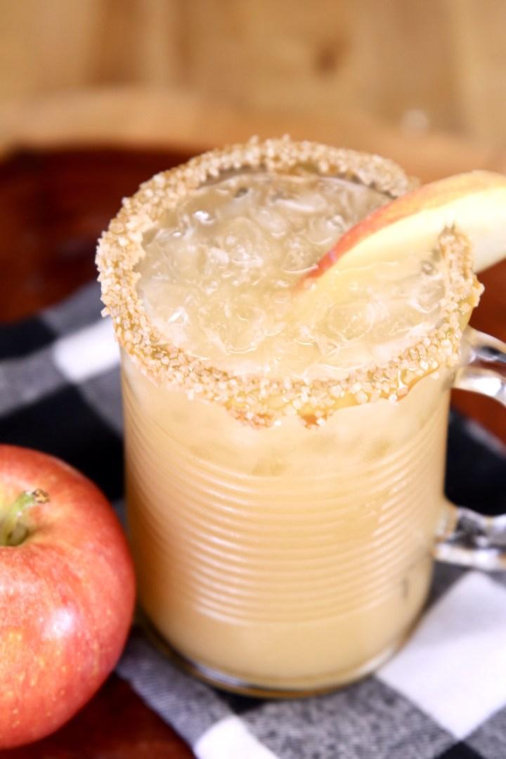 apple slice garnished caramel cocktail in a glass