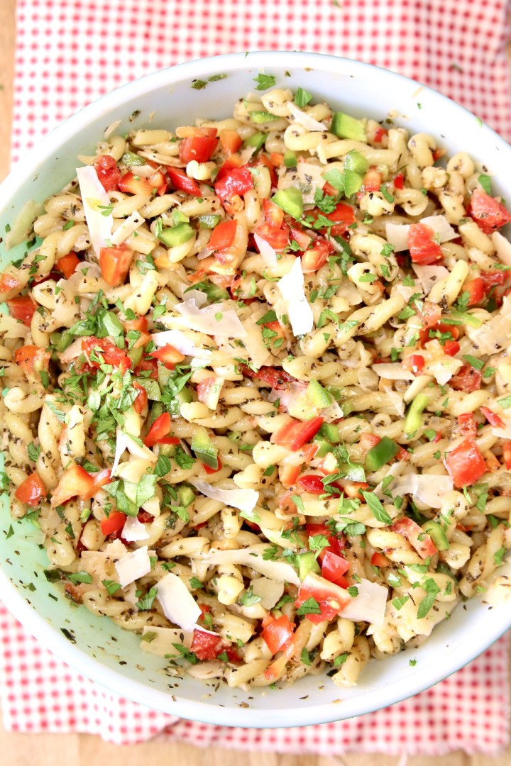 bowl of pasta salad with tomatoes, peppers, cheese on a red napkin