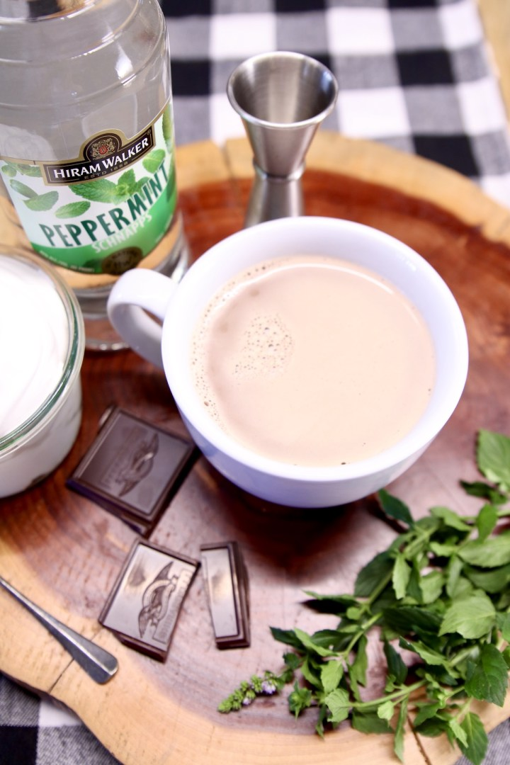hot chocolate in a mug on a wood board with peppermint schnapps