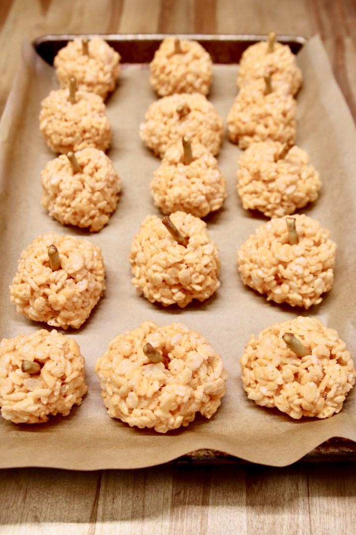 orange rice krispies balls with pretzel sticks