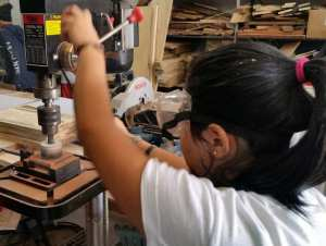 Girls making wooden bracelets in the workshop