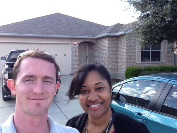 young couple taking a picture in front of house