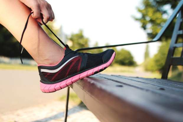 person tying running shoes to make period suck less