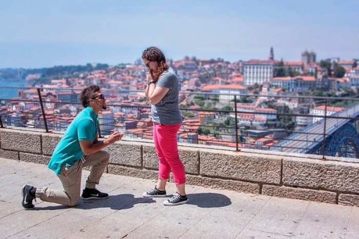 boy on one knee proposing to girl with city in background getting ready for wedding prep
