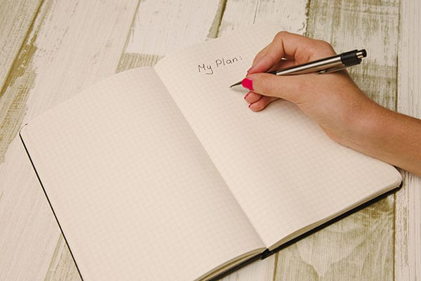 woman writing list in notebook to boot your confidence