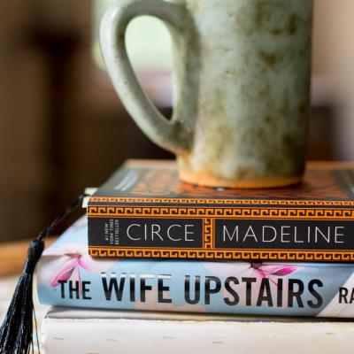 A stack of three novels, from this June and July Reading Recap with a green mug of coffee sitting on top.