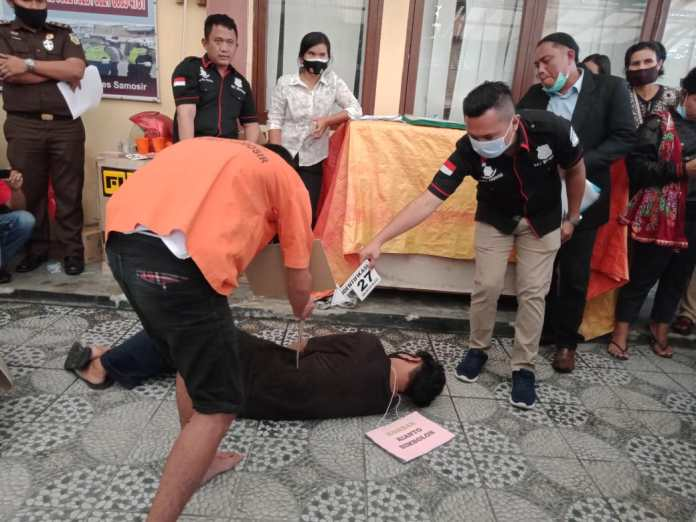 Salah seorang pelaku pembuhan memperagakan adegan penusukan terhadap korban dalam adegan rekonstruksi kasus pembunuhan Rianto Simbolon (f:mistar/Sawangin Sinurat)
