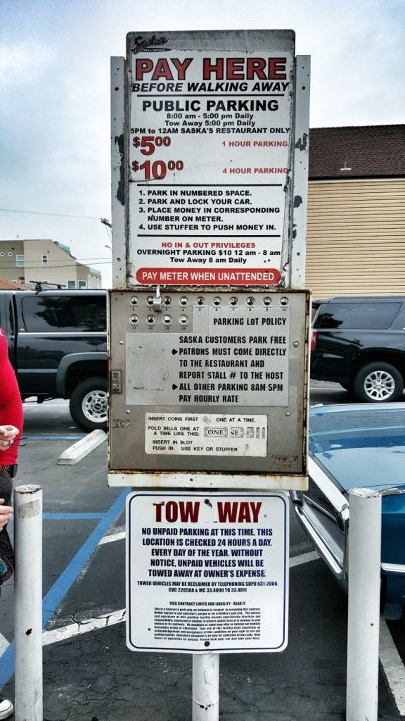 Frage!! Was ist das für ein Apparat?  Man soll es nicht für möglich halten, aber dies ist ein Parkautomat. :))  1. Man stellt den Wagen auf einen Parkplatz ab und merkt sich die Nummer, die dort auf dem Boden steht.  2. Man steckt in die Öffnung mit der gleichen Nummer in dem Automaten die vorgeschriebene Parkgebühr.  3. Der Automat wird stündlich kontrolliert. Sollte kein Geld drin sein, wird der Wagen abgeschleppt.  Also wir haben auch ein wenig gebraucht, um das Verfahren bei der Menge an Text zu verstehen. :))