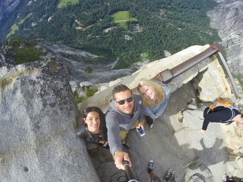 Herzlich Willkommen auf dem Glacier Point. Wie man aus dieser Perspektive sehr gut sehen kann, geht es hinter uns direkt steil bergab in die Tiefe. Genauer gesagt, über 2.000 Meter. Menschen mit Höhenangst sollten lieber nicht zu nah ans Geländer gehen.