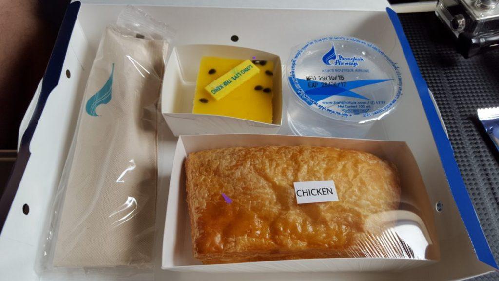 """An Bord gab es dann auch noch eine Lunchbox mit einem kleinen Blätterteig Snack mit Chicken-Füllung und einem kleinen Stück Kuchen mit der Aufschrift: """"Long Live The King"""". Kleine Anmerkung am Rande: Heute war auch der Geburtstag des Königs von Thailand."""