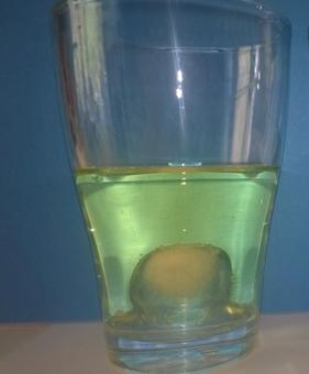 Ein Eiswürfel taucht in einem Glas mit Pflanzenöl.
