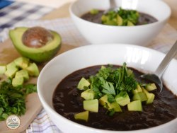 black bean soup in a white bowl with avocado and parsley