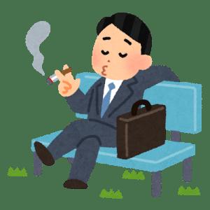 仕事をサボってベンチでタバコを吸う男性