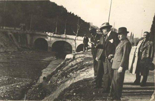 Αθήνα, 1937. Κάλυψη Ιλισού Ο Διοικητής Πρωτευούσης (επί δικτατορίας Μεταξά) Κωνσταντίνος Κοτζιάς επισκέπτεται τα έργα της κάλυψης Ιλισού μπροστά Στις αρχές του 20ου αιώνα ολόκληρη η περιοχή μεταξύ Ιλισού και Υμηττού είχε κηρυχθεί αναδασωτέα και είχε φυτευτεί. Στη δεκαετία του '50 ολοκληρώθηκε η κάλυψη της κοίτης του ποταμού και τη θέση του ποταμού πήραν οι οδοί Μιχαλακοπούλου, Βασιλέως Κωνσταντίνου και Καλλιρόης. Το έργο είχε ξεκινήσει το 1939 και το θεμελίωσε ο Μεταξάς με τη χαρακτηριστική φράση : «Θάπτομεν τον Ιλισόν». Πηγή: Η Αθήνα μέσα στο χρόνο