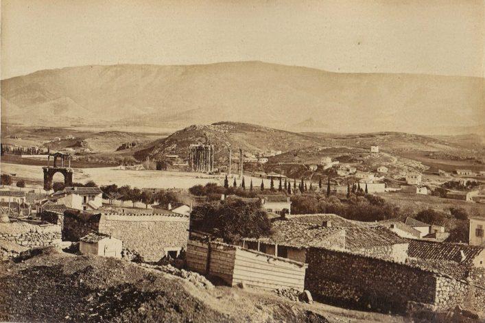 Άποψη από τους πρόποδες της Ακρόπολης προς τον Αρδηττό και τον Υμηττό (περ. 1870) Διακρίνονται η πύλη του Αδριανού, το Ολυμπιείον, η θέση του Παναθηναϊκού Σταδίου, που δεν έχει ακόμα αποκαλυφθεί (το κοίλο προς τα αριστερά της φωτογραφίας) και ακόμα πιο αριστερά, στα κυπαρίσσια, το Προτεσταντικό Νεκροταφείο.