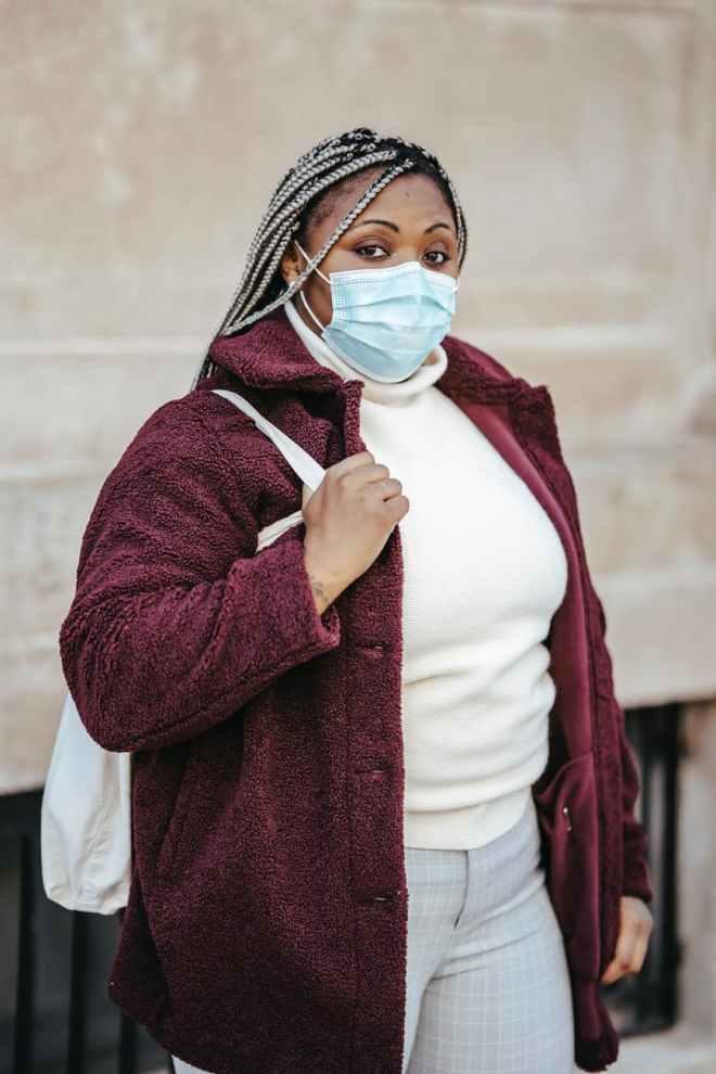 black lady wearing medical mask in street