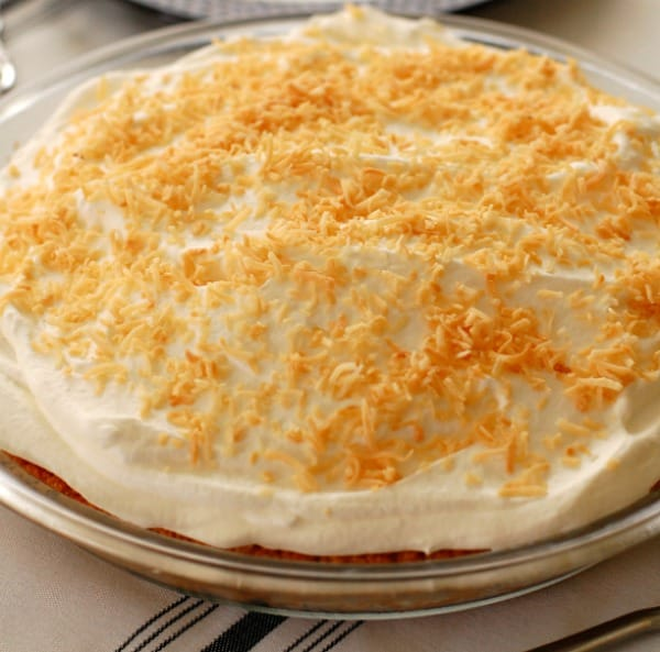 With a thick layer of sweetened whipped cream flavored with coconut rum and a sprinkling of toasted coconut, piña colada pie is ready to be sliced and served.   mjbakesalot.com