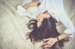 Woman comfortably sleeping beside her dog