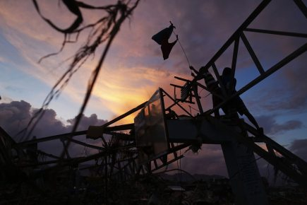 Survivors place a makeshift flag over a sports hall destroyed by Typhoon Haiyan, in Tacloban
