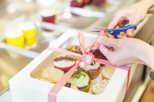 Hand packing many kinds of cupcakes as a present for a wedding o