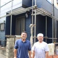 塗装後の家の前で写真を撮る職人と営業
