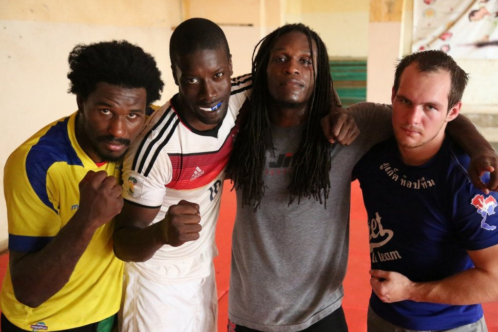 Muay thai coach looks over students and mma fighters in africa