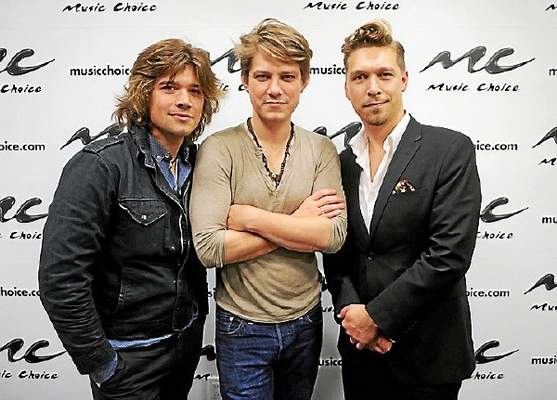 "NEW YORK, NY - Zac Hanson (from left), Taylor Hanson and Isaac Hanson of the band Hanson visit ""U&A"" at Music Choice on April 12, 2013, in New York City. (Photo by Jamie McCarthy/Getty Images)"