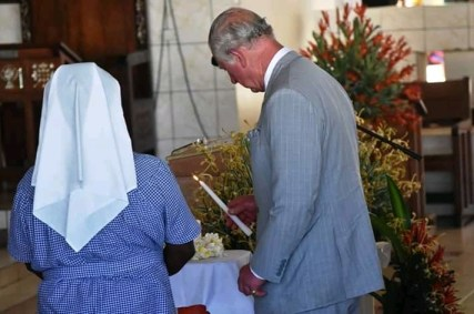 Prince Charles lighting a candle to signify the launch of the 16 days of activism during the service at the Cathedral